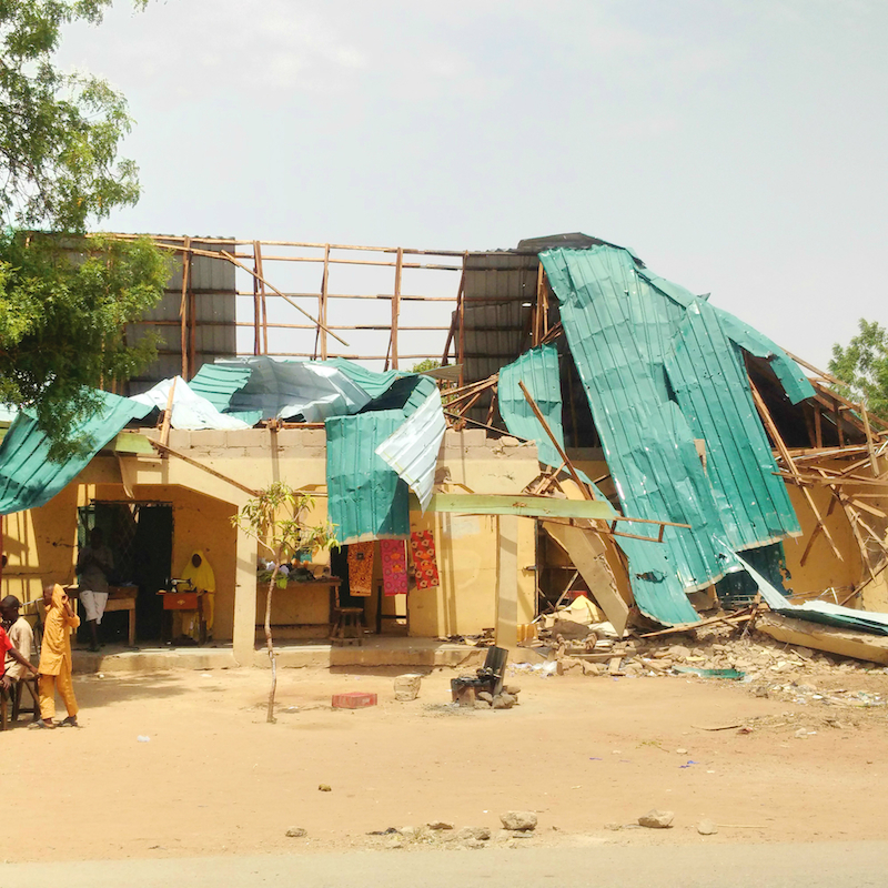Girl sewing in shop destroyed by Boko Haram site