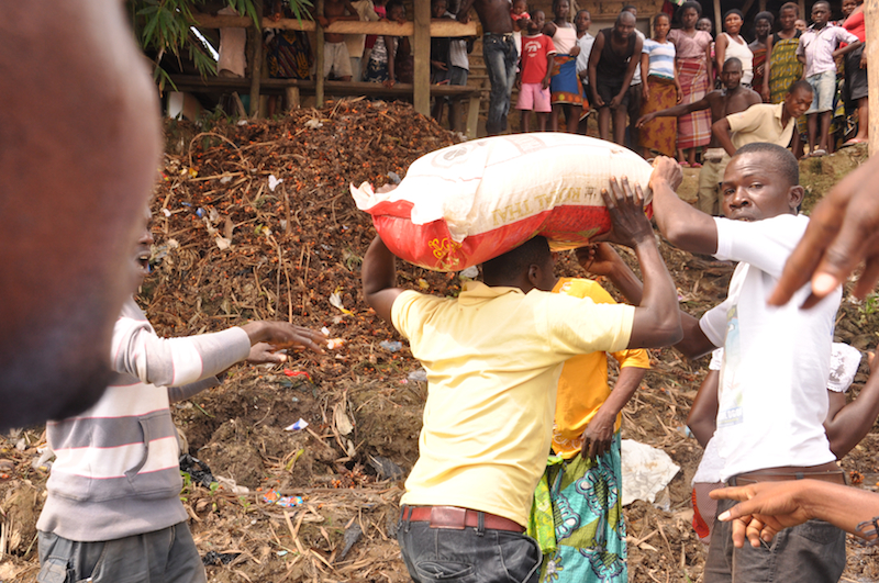 Men helping women carry the bags of rice