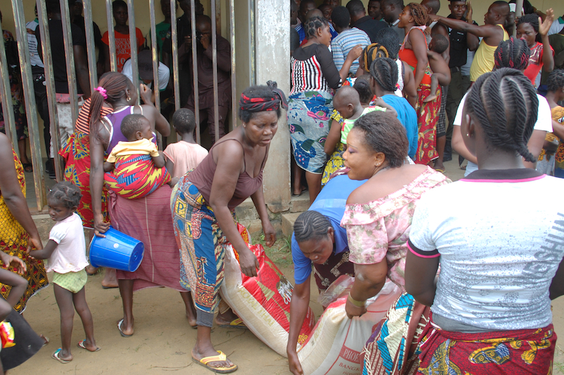 People carrying bags of rice home